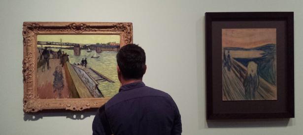 Een bezoeker kijkt in het Van Gogh Museum naar Vincent van Goghs De brug van Trinquetaille en Edvard Munchs De schreeuw.