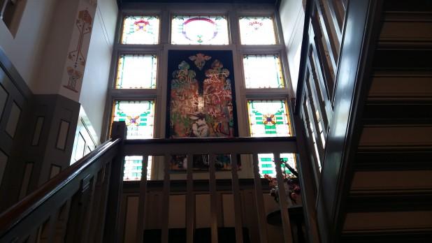 Trappenhuis met glas-in-loodramen en een Banksy.